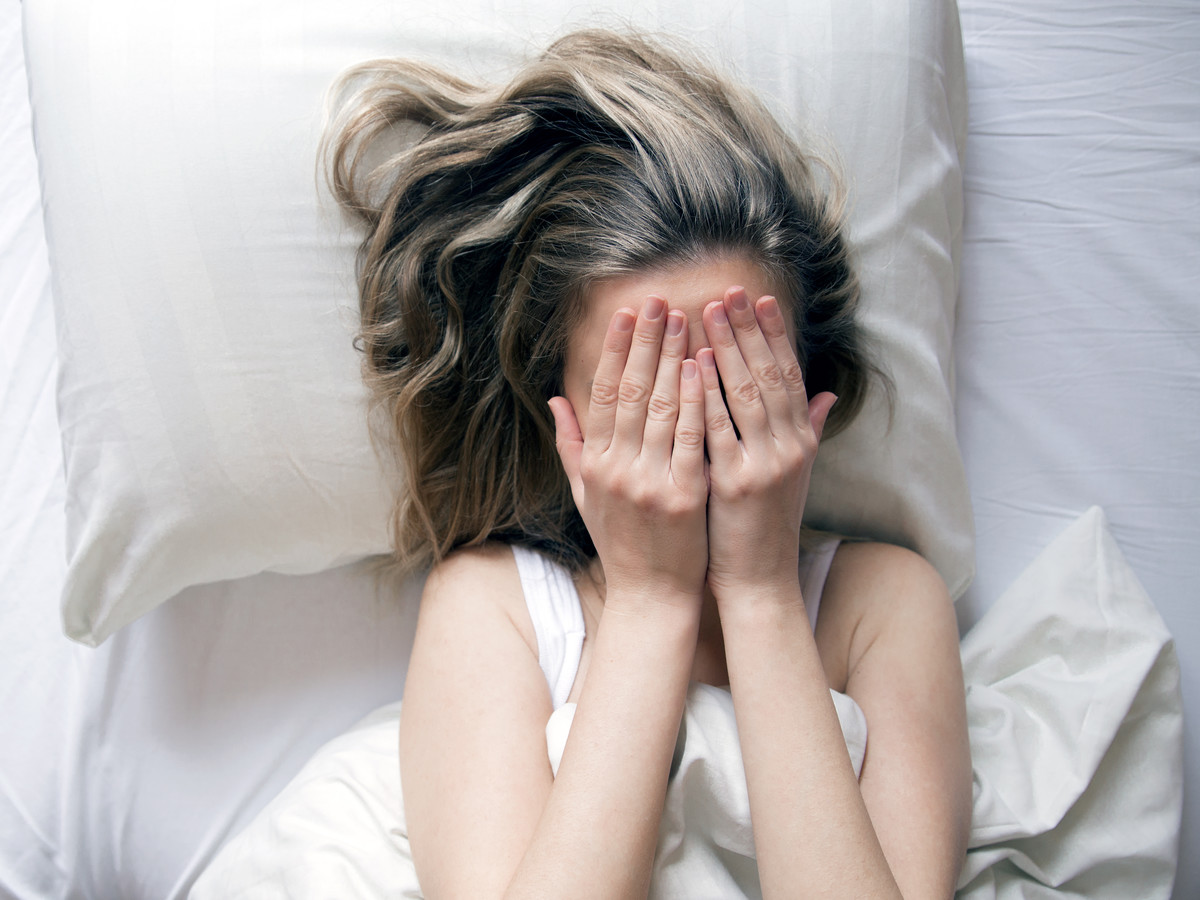 Woman in bed, hands over face