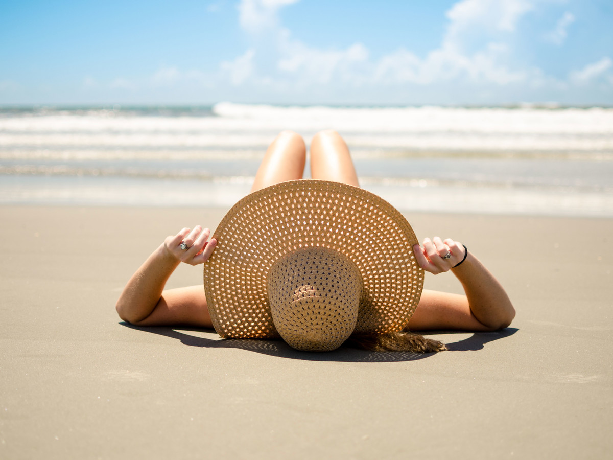 Woman Sunbathing on the Beach with a Floppy Hat