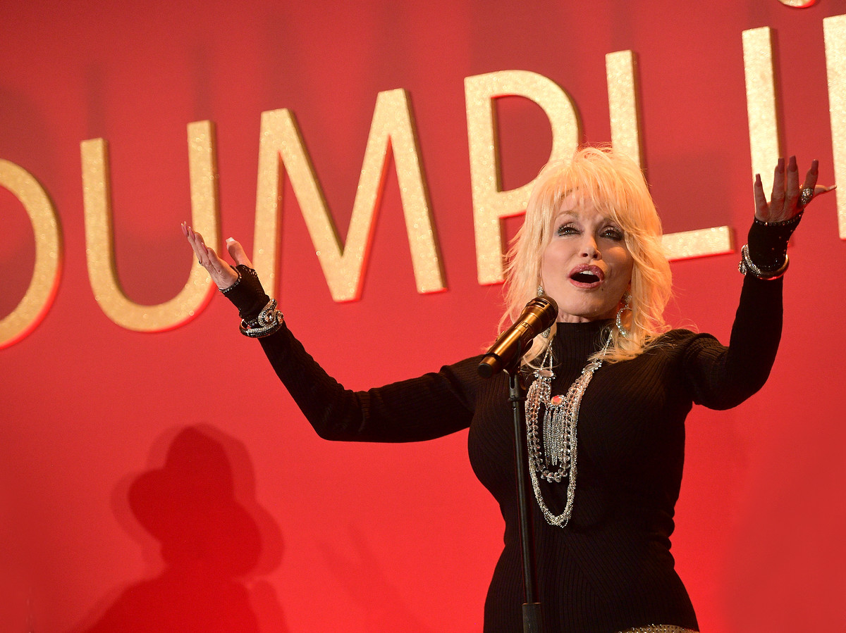 Dolly Parton in front of Dumplin Sign