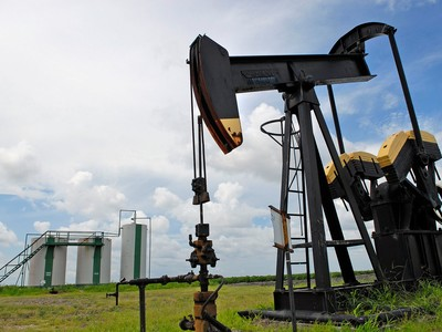 Oil pump jack pumps, front, and storage tanks, in the distance, are seen on a farm near Corpus Christi, Texas, July 14, 2006.