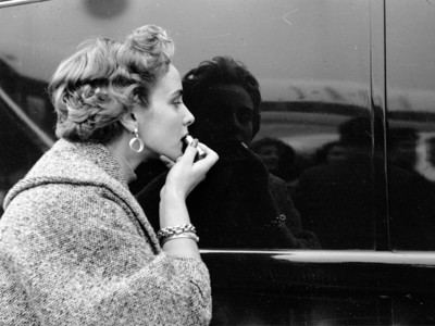 Woman applying lipstick using car reflection