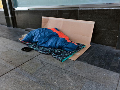 Person on Street in Sleeping Bag
