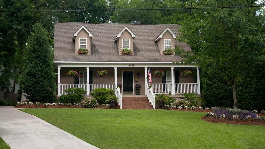 Front of house with hanging baskets, window boxes, and flag.