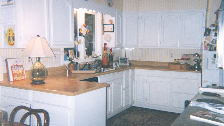 dated kitchen with white cabinets, wooden countertops in a u-shape with a window over the sink