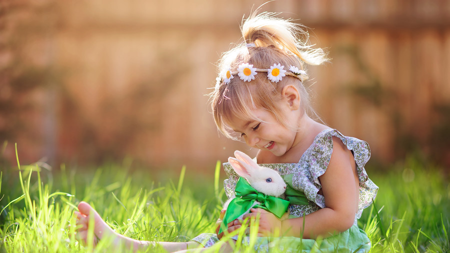 Girl with bunny sitting in the grass