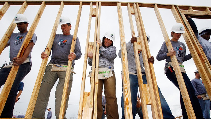 volunteers putting up framing for house