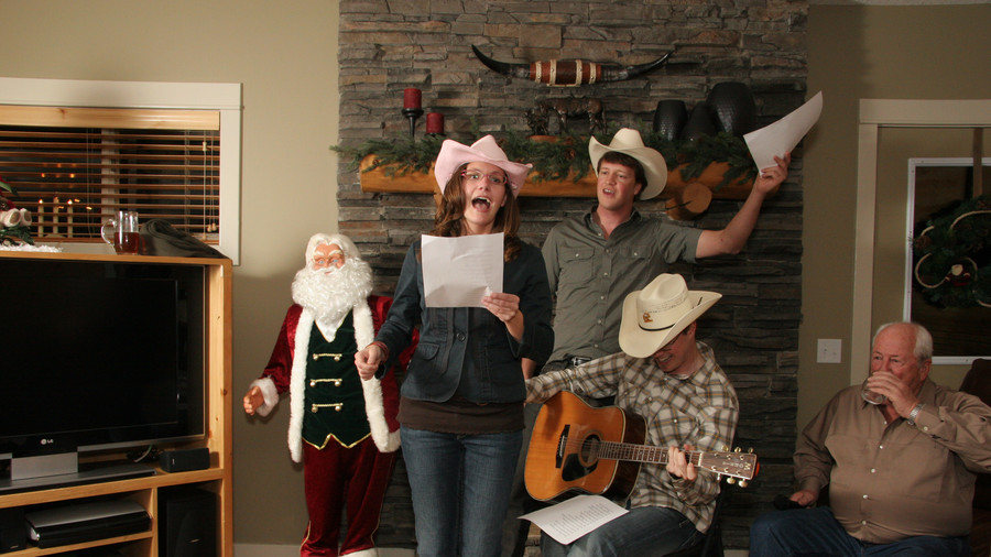 Family singing carols wearing cowboy hatsFamily