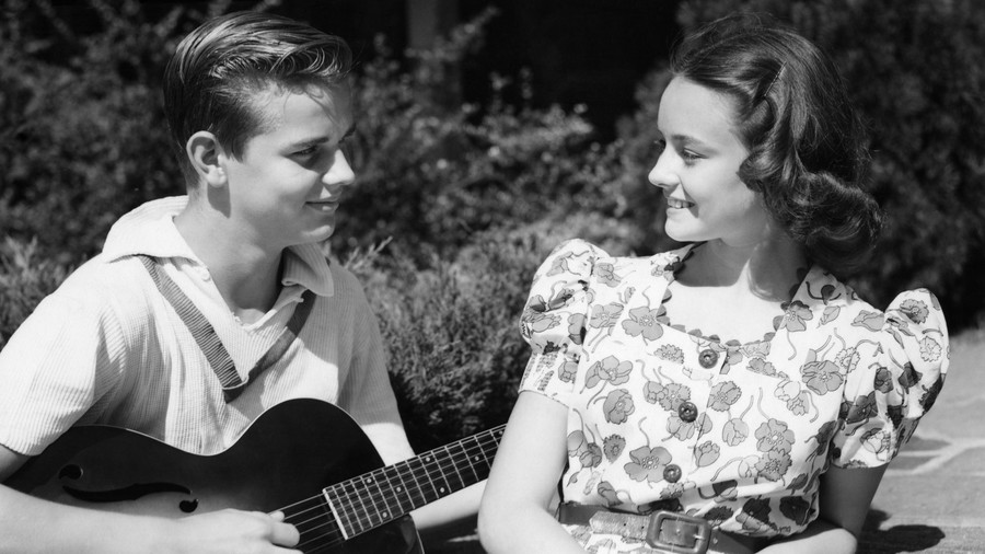 Boy playing guitar for girl