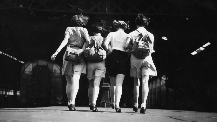 Four women walking with arms linked