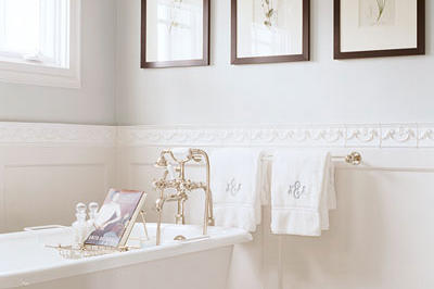 three, framed pictures are hung horizontally on the wall above a claw foot tub in a white bathroom