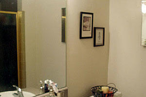 an outdated bathroom with gray formica countertops and a mirror before it is to be renovated