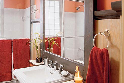an oversized mirror with a dull metal frame brings in a ton of reflected light to a small bath that's decorated in peach, and ruby tones with natural, beaded-wood walls and a white pedestal sink