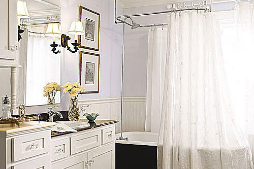 airy white bathroom remodel with a black, clawfoot tub with a white shower curtain and a built-in custom sink cabinet with clear drawer knobs