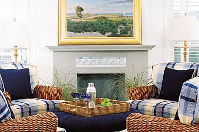 Two windows flank each side of the fireplace with a gray hearth. Also, white walls brighten up the space with yellow and blue large plaid cushions on wicker arm chairs.