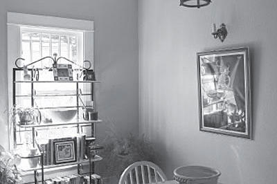 a before photo of a kitchen space with a baker's rack placed in front of a window and a table with two chairs