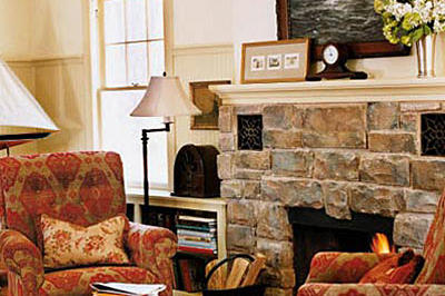 Large, natural stones around the hearth update this fireplace's style while red and tan velvet fabric decorates the arm chairs that are placed on either side.