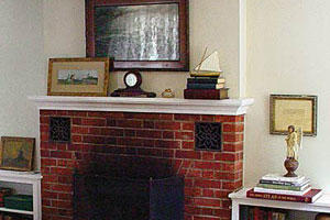 a before photo of a old brick fireplace with blackened bricks in a family room with white walls