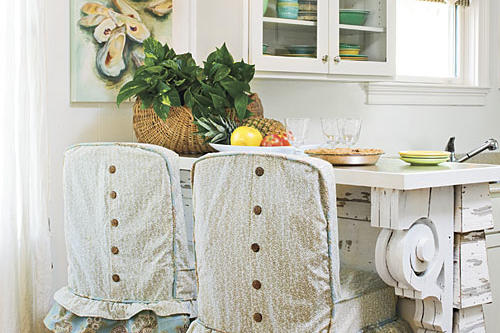 ruffles line the bottom of the casual, cottage-style slipcovers with brown buttons running vertically down the back of each slipcover