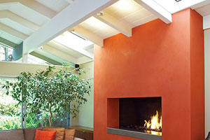 A vibrant tomato bisque-hued plaster added to this fireplace remodel turned the hearth into a modern showpiece in this living room.