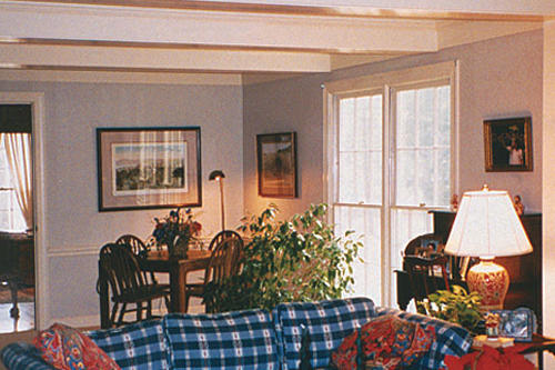 a living room with a blue and white checkered couch before a design makeover