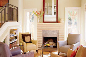 In the living room, a bright red mirror hangs above a cast concrete fireplace. There are four light-colored, leather arm chairs surround stacked coffee tables that are in front of the fireplace.