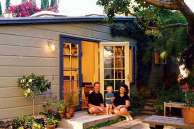 shed turned into a guest suite with a tan exterior and blue painted French double doors opened into a patio