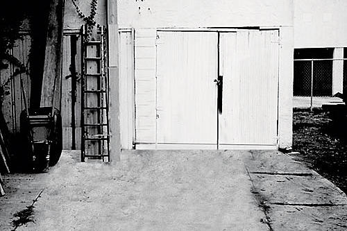old, freestanding garage with a set of white doors
