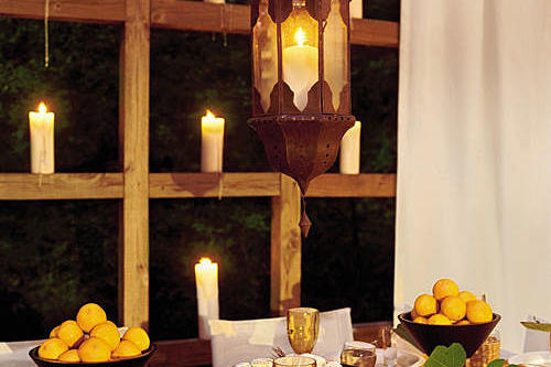 white candles are placed on the wooden ledges surrounding the deck with a table decorated with lemons in bowls, a hanging lantern, white plates and wine glasses