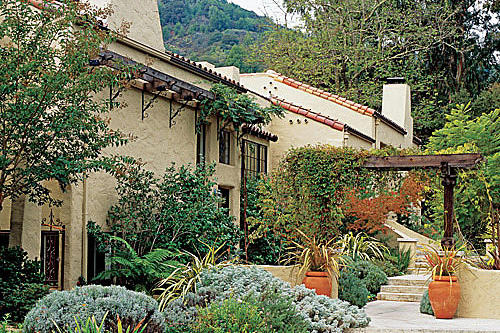 lush, planting beds, bushes and container plants line the front of the Mediterranean style home