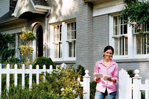 young homeowner in front of her painted brick house with a white picket fence in front