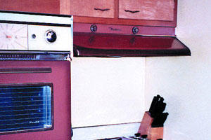 outdated kitchen cabinets with an old oven and stove in burgundy colors