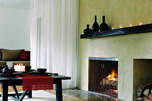 sleek, stucco-covered fireplace with a dark wood mantel and a storage place for a stack of wood in this lounge space