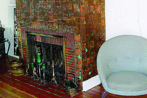 dated fireplace covered in gold and red wallpaper