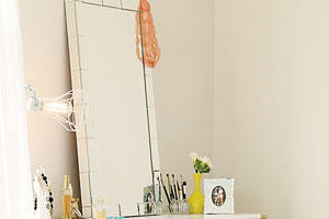 a rectangular glass-framed mirror sits atop a yellow desk with a variety of perfume, make up brushes, photo frames and jewelry decorate the top of it