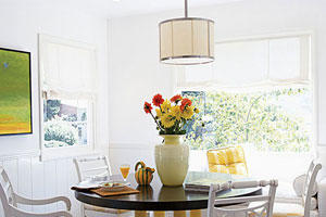 A bright, white dining room with crisp, white cloth shades over the windows and a large circular wooden dining room table with pale, yellow legs and white chairs surround it