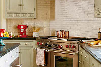 stainless steel gas stove range in a kitchen with creamy, subway tiles as the backsplash behind the stove and light, tan kitchen cabinetry to the left and right of it
