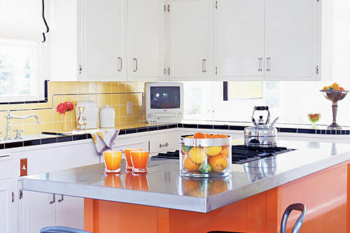 a bright, orange, modern kitchen island  with a steel countertop sits in the middle of this updated, vintage style kitchen