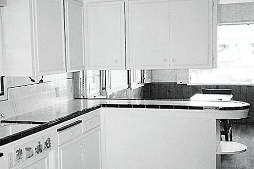 outdated kitchen with a l-shaped cabinet layout that divides the breakfast room from the kitchen