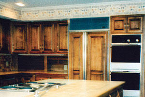 oversized kitchen island with brown cabinets with an old oven and old florescent lighting in the ceiling