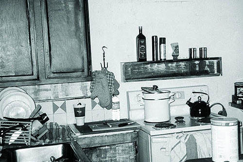 original photo of an old kitchen in a beach shack with cramped space