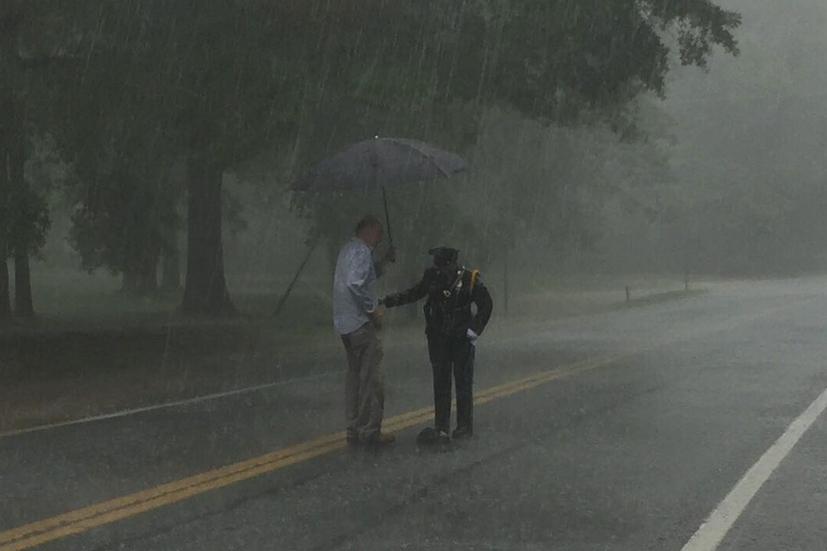 The Reason This Police Officer Is Standing in the Middle of the Road in the Rain Will Make Your Day