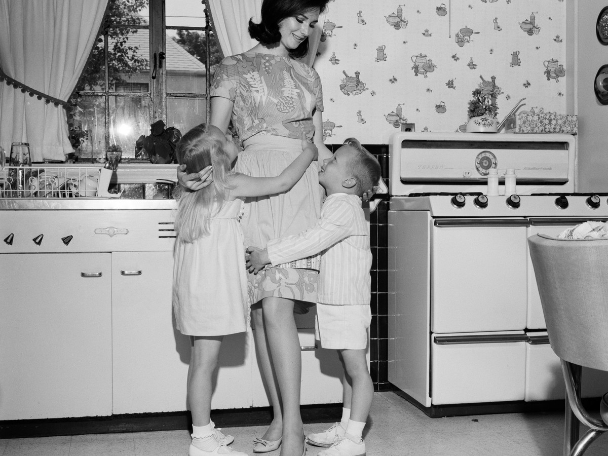 Children hugging mom in kitchen