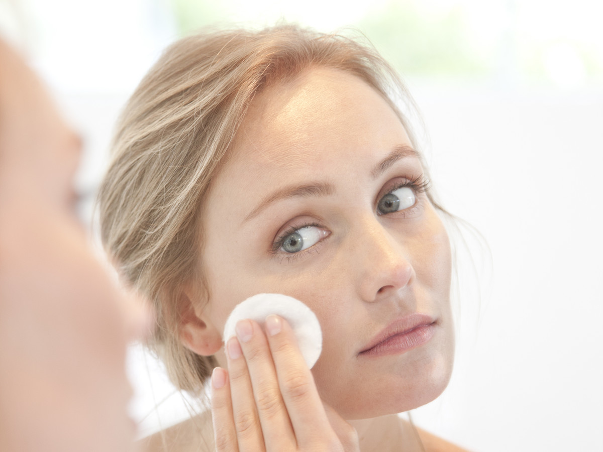 Woman washing face with cotton pad