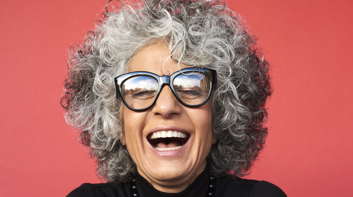 Smiling Woman with Gray Hair on Red Background