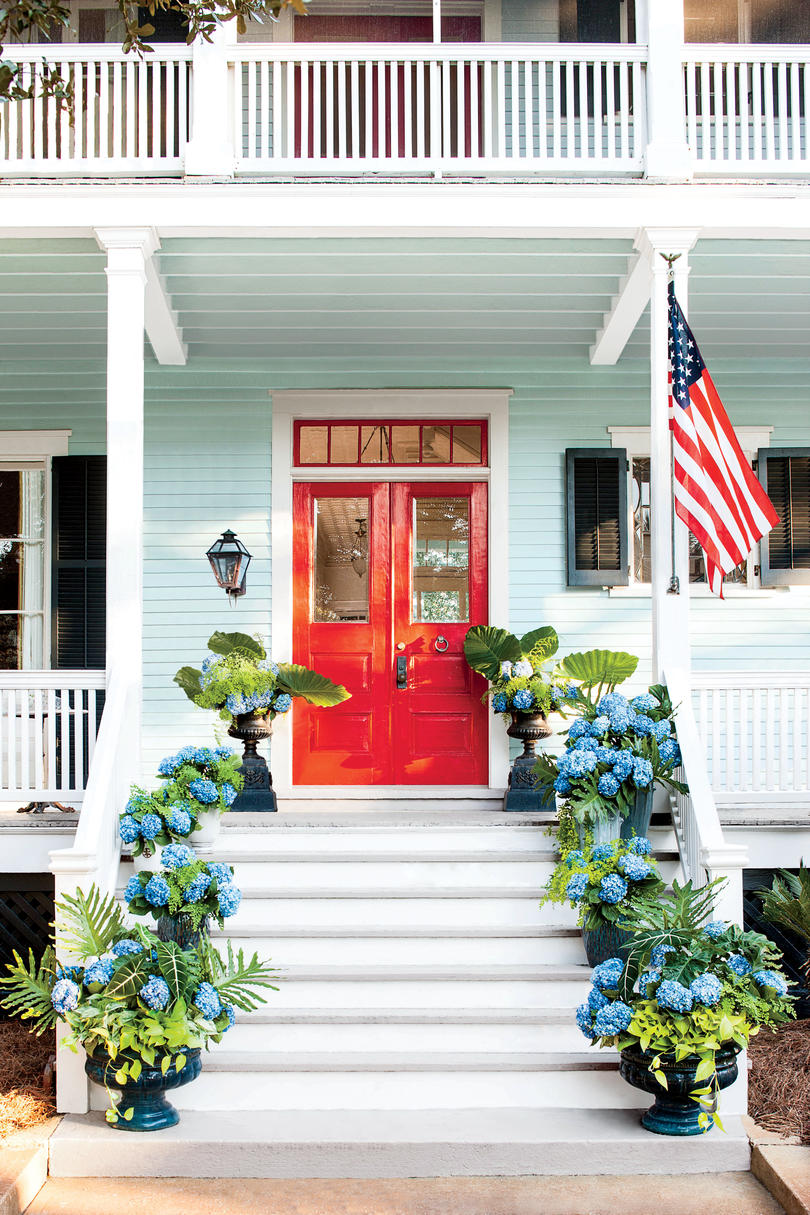 Brilliant Red Front Door on a Light Blue House with Containers of Hydrangeas