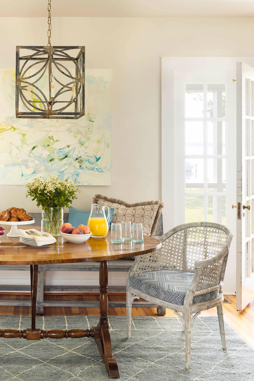 """We wanted to bring in warm woods with age to match the island,"" says Molster of her decision to use an antique table in the dining nook off the kitchen. To dress down the table's formality, the designer brought in a simple wooden bench and vintage chairs"