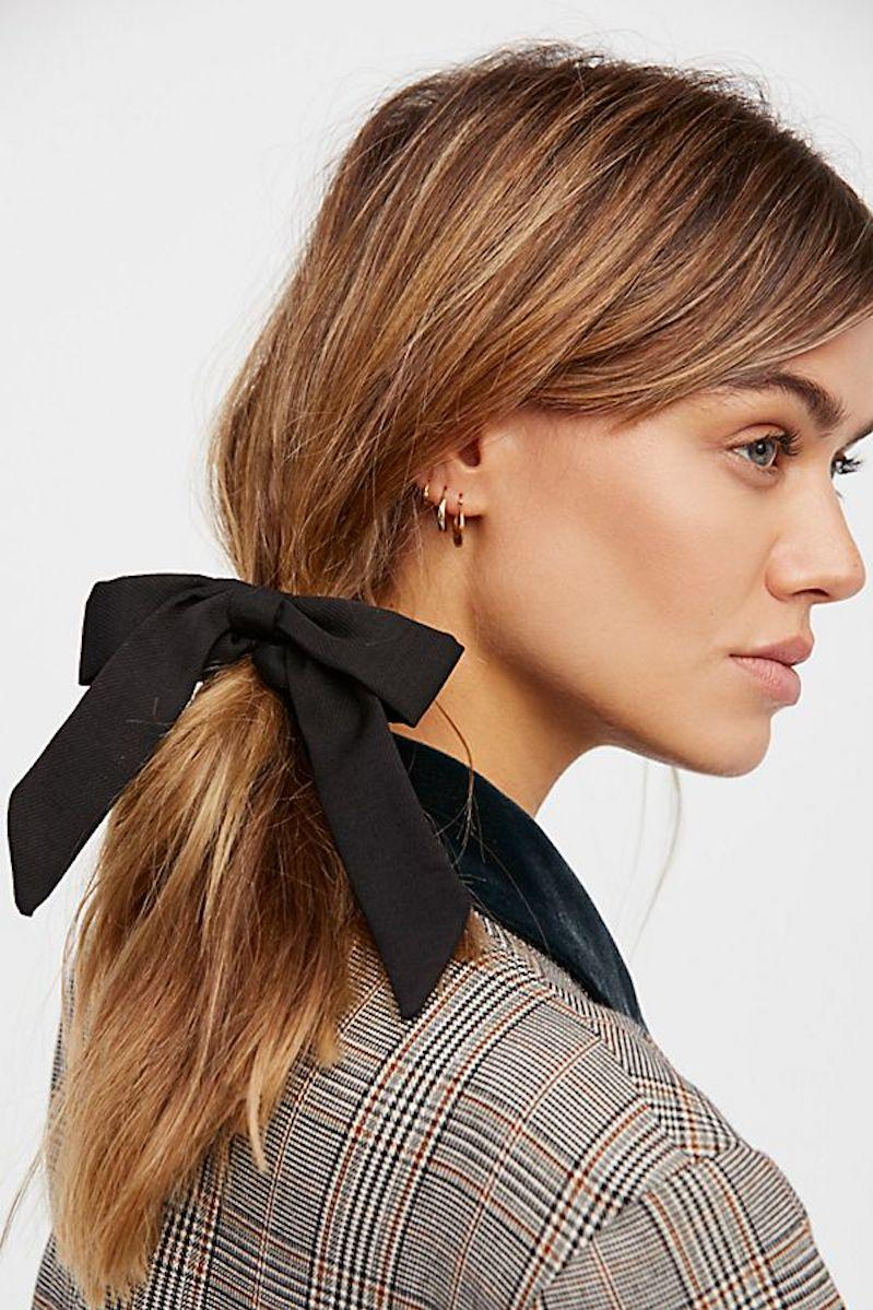 Woman wearing ponytail with bow hair scrunchie