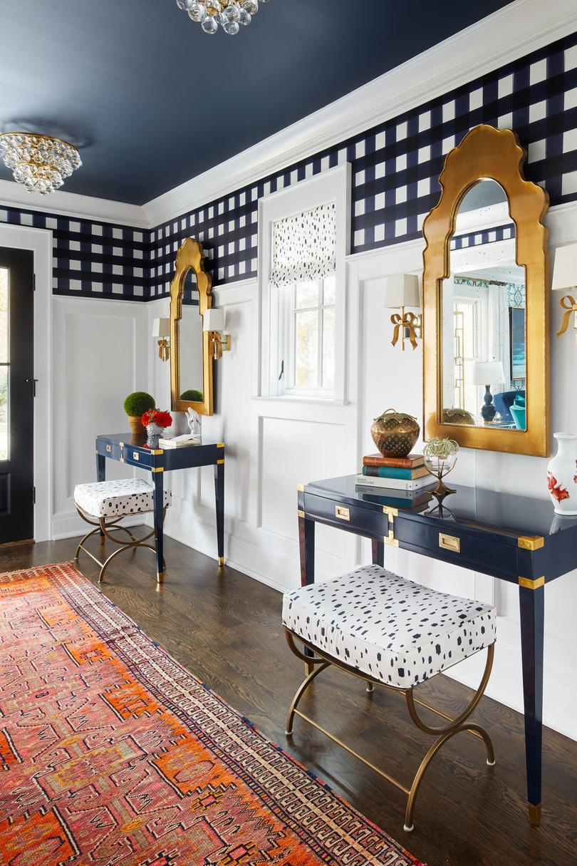 The foyer features tall wainscoting with geometric wallpaper at the top, a deep blue ceiling, and playful details, such as the bow-adorned sconces, balanced by more masculine aspects, such as the buffalo check wallpaper.