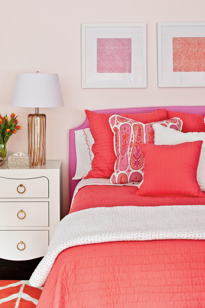 Bright, warm colors in fabrics and accesories really pop against white walls in this bold bedroom.