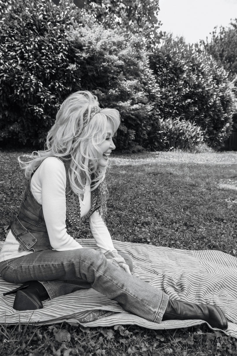 Dolly Parton sitting outside on blanket